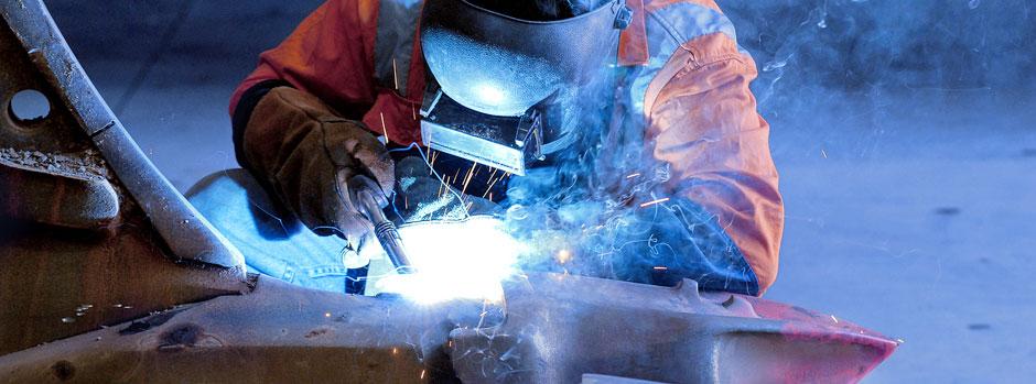 Welder Repairing Earthmoving Bucket