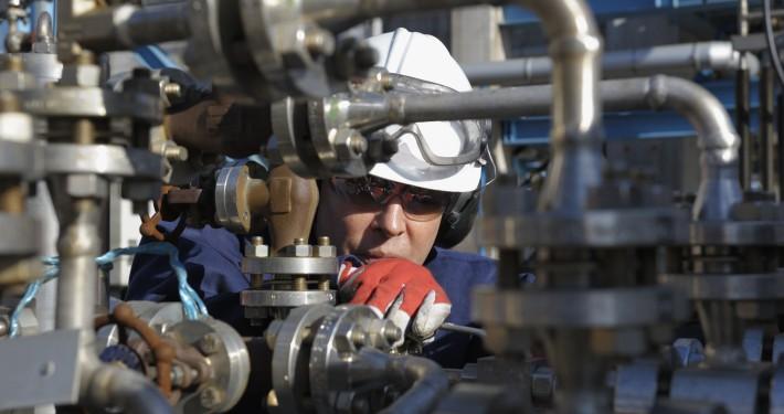 engineer standing behind pipeline machinery inside oil refinery